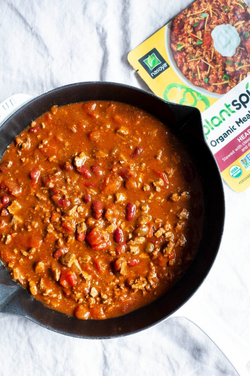 A large, cast iron skillet is filled with a bean-based chili.