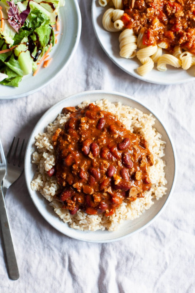 Nasoya's Plantspired Meal Solutions feature an easy vegan chili, which has been scooped onto a plate of brown rice.